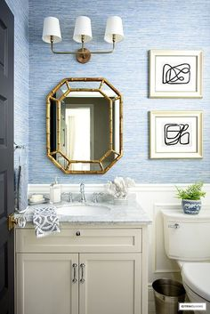 Blue and white coastal-chic bathroom with white vanity, silver hardware and faucet, gold mirror and lighting and blue grasscloth wallpaper. #bathroom #smallbathroom #grasscloth #bluebathrrom #kidsbathroom #powderroom #bluewallpaper #wallpaper