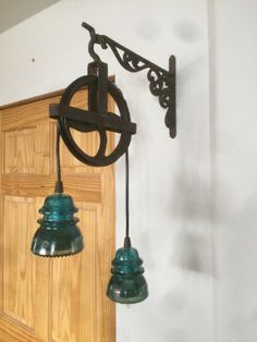 Two antique green insulator lights on an antique steel well pulley hanging f. - Two antique green insulator lights on an antique steel well pulley hanging from a heavy cast - Antique Decor, Antique Glass, Vintage Decor, Rustic Decor, Farmhouse Decor, Antique Jewelry, Insulator Lights, Glass Insulators, Rustic Lighting
