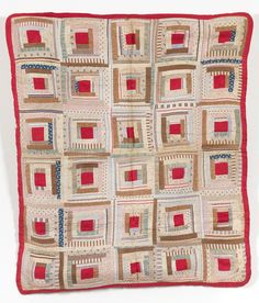 Log Cabin Cot Coverlet.  Maker:Unknown Date:1850 - 1900  This piece is a Log Cabin cot coverlet with bound edges and hand-sewn on a foundation in a 'courthouse steps' arrangement. Farbics present in the piece include Turkey red cotton, and printed and woven dress and shirting cottons. The fabrics are red, brown and blue in colour.