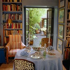 A table is laid for lunch in the small library where the French windows open onto a courtyard paved with slate and dominated by bamboo in tubs - Photographer: Fritz von der Schulenburg - Designer/Stylist: John Stefanidis - Country: England - Location: London - John Stefanidis 221/344