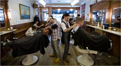 Cool wooden flooring and work stations, with old school white barbers chairs. White tiles walls to match. Barbers shop.