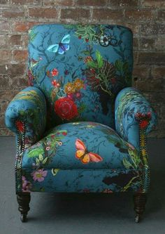 Garden painting on a blue overstuffed chair. Beautiful floral with butterflies, blossoms and dragonflies.