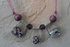 what a fun idea! use the spring from a wood clothes pin to hang beads on a necklace