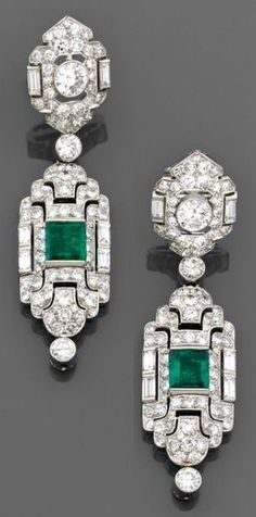 A Pair of Art Deco diamond, emerald and platinum and gold pendant earrings, circa 1930. Of Persian design, each set with brilliant-cut and baguette diamonds, the pendant centring a square-shaped emerald, suspending an articulated bezel-set diamond.
