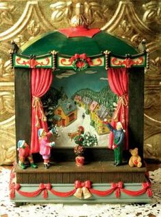"Flurries Music Box  Gleeful children peer through a parlour picture window into a wintry wonderland. Blowing ""snow"" dances upon a hand painted village scene. Plays 8 classic Christmas songs. 11""."