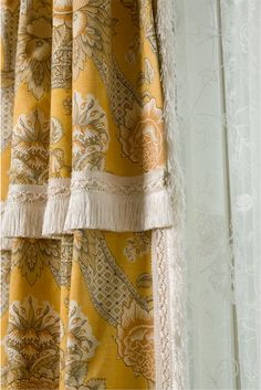 Floor to ceiling traverse draperies with a shawl valance all in yellow fleur toile trimmed with brush fringe and sheers mounted underneath.