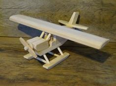 Handmade original design wood toy Alaska bush plane. 13 1/2 inches wide and 17 1/2 inches long, propeller spins, and comes with 2 little wood