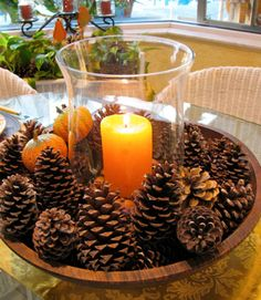 Simpele maar sfeervolle #woondecoratie. Zet een glazen #vaas of #windlicht met een #kaars in een grote #schaal en vul de schaal aan met #dennenappels. #glass #candle #cones #bowl