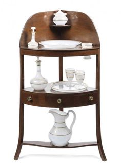 A George III Mahogany Corner Washstand with Opalescent Glass Fittings, the stand having shaped back splash fitted with a corner shelf to fit a single bottle above larger shelf having three circular openings containing a single drawer, the lower stretcher with raised ring to accommodate ewer, together with a opalescent glass, ewer, bowl, plate, decanter, two goblets, perfume bottle, covered dish and a tumbler.
