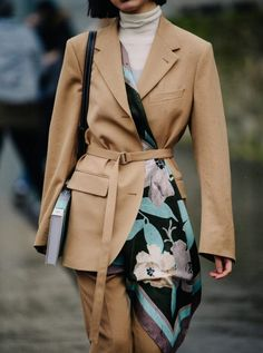 d872b350dd4 Street style  beige camel pant suit with belted silk flower print scarf and  white turtleneck sweater and black leather bag.