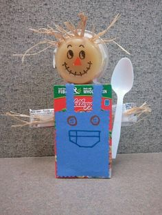 Scarecrow snack made of individual cereal box, applesauce cup, and a fruit rollup.