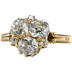 This unique Victorian ring consists of three Old Mine cut diamonds,which are approximately 1 carat each (totaling approximately 3 carats in total diamond weight) along with three small accent diamonds set in between the larger ones in 18 karat yellow gold, circa 1890s.