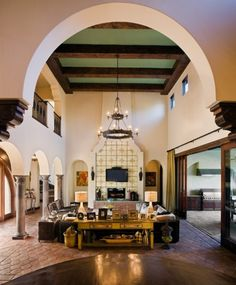 A beautiful Mediterranean-inspired living space, with columns and arches providing an open entry into the room, which also boasts a beamed, two-story ceiling (via 7112 Greenshores - mediterranean - living room - austin - by Vanguard Studio Inc.)
