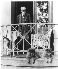 Sigmund Freud standing on balcony with two dogs, c. 1935