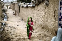 A young Afghan #refugee makes her way in a slum on the outskirts of #Islamabad, the Pakistani capital. (Muhammed Muheisen, Associated Press / August 14, 2012)
