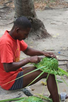 Local Salesman making hats out of palm tree leaves