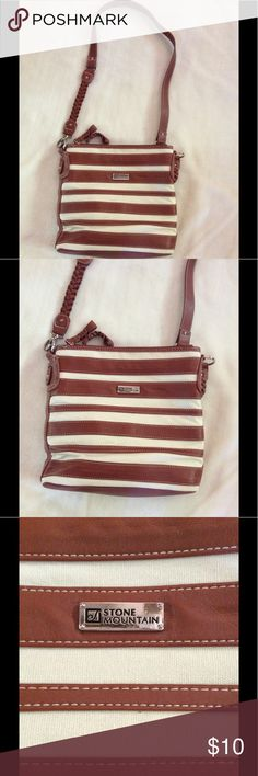 🆕 StoneMountain Brown and white cross body purse Brown and white StoneMountain purse. Cross body style. Three deep pockets. Two of the with zippers. Middle pocket has a snap closure, one small side zipper pocket and on the other spider side side two elastic pockets. Two small flaws:  a slight blemish on the top of front and back, barely noticeable. Can see in last two pictures.     Measurements:  Strap length:  23 1/2 inches  Measurements of purse:  Width:  11 inches.   Length:  10 inches…