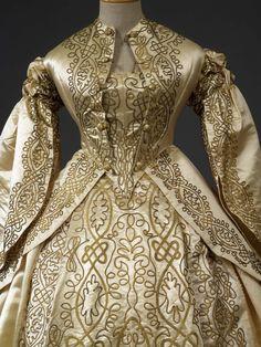 Abito da sposa in tre pezzi (corpetto, giacca, gonna) in raso di seta avorio con applicazione di due tipi di spighette in filo metallico dorato a disegni di nodi di ispirazione rinascimentale.