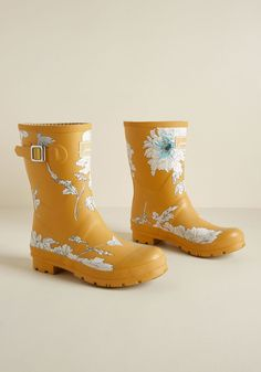Just Splashing Through Rain Boot in Yellow Floral - En route to your destination with plenty of time to spare? Luckily you're clad in these mustard yellow rain boots by Joules, for the child in your heart wants to splash! Touting silver buckles, treaded soles, and bright white flowers, these waterproof rubber boots make greeting puddles a giddy endeavor #mustardyellow #rainboots #florals #modcloth