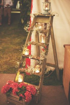 Wooden ladder decorated with flowers, candles and lights