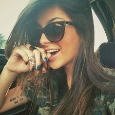 Camo Tee Shirt, Blue Nails, Mid Ring, Thich Band Ring, Straight Side Part Hair, Cat Eye Sunglasses and Upper Arm Tattoo. #accessories