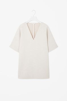 With a deep v-neck, this tunic top is made from a woven material layered with a sheer finish. An oversized fit, it has kimono short sleeves and a straight hemline.