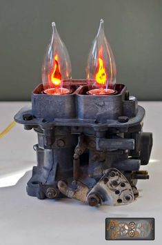 This lamp is one of a kind. Made from an old VW 2 barrel carburetor that was damaged beyond repair, it houses 2 standard (E26) flicker-flame bulbs and is controlled by a simple on/off toggle switch behind the bulbs. Ideal for any car enthusiasts desk, or great in an industrial