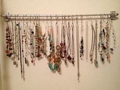 Use a curtain rod and Christmas ornament hooks for necklace storage. You could also use craft wire.