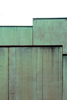 """""""The walls are clad with large pre-fabricated slabs of concrete. Mixed with pulverized limestone and copper, the principal materials used to build the villa, the concrete cladding will turn green. Water enriched with copper ions running down the façade w Concrete Cladding, Metal Cladding, Exterior Cladding, Wall Cladding, Concrete Floors, Green Front Doors, Front Door Colors, Winterthur, Building Facade"""