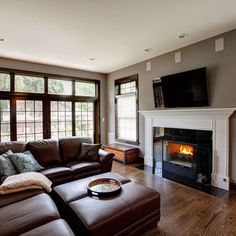brown couch and hardwood floors, gray wall