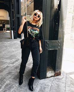 T-shirt vintage e calça preta pode parecer básico, mas não precisa ser! Com um nó na camiseta, a barra da calça dobrada, uma bolsa de corrente e bota de salto, o look fica muito mais estiloso. Nicole Alyse - t-shirt-vintage-calça-preta - t-shirt-vintage - meia estação - street style