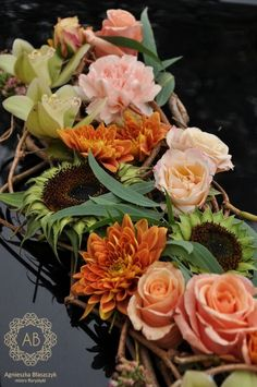 Close up detail of a rich floral wedding car decoration with green cymbidium orchids, sunflowers, roses, carnations and chrysanthemums in tones of pink and burnt orange. By Agnieszka Blaszczyk at abkwiaty.pl |