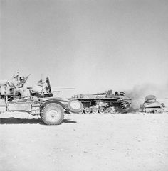 A lorry-mounted 2-pdr anti-tank gun passes a destroyed German PzKpfw tank in the Western Desert, 2 June 1942.