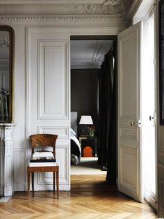 light to dark via Jonny Valiant | light hallway with white walls and crown moldings leading into a dark bedroom | vintage wooden chair | wooden herringbone floors | panelled doors | Parisian style interior