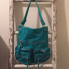 Fun turquoise canvas bag This bag does it all! Thick durable turquoise fabric with tons of zippers and pockets. Great book bag or beach bag. Super versatile -- just needs a new home! Bags Satchels