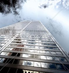 low angle view of a tall corporate building against cloudy sky. - Low angle shot of a elegant tall commercial building against cloudy sky.