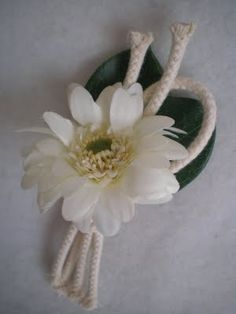 Knotted rope, leaves, and a mini daisy is a sailor's dream boutonniere.