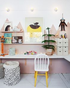 Obsessed with this adorable kid's workspace! Pink mountain mural and long built in white desk, yellow chair. Lots of art, shelves and storage.