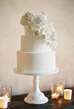 Brides.com: . Drawing inspiration from the bride's wedding gown, Melody Brandon of Sweet & Saucy Shop created this all-white cake featuring scalloped fondant lace and a cluster of white sugar flowers that matched her bridal bouquet.   $15 per slice, Sweet & Saucy Shop