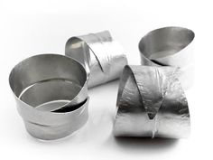 Add a subtle elegance to table settings with handmade stainless steel curled leaf napkin rings. Designed by HAMMERHEADdesigns on Etsy.