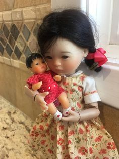 Ten Ping wearing her new dress and holding her doll, a repainted vintage Shackman doll.