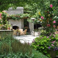 Outdoor fireplace framed pergola; also mandevilla, petunias, and sweet potato vine in the foreground. Low walls lend sense of enclosure, an oasis in a secret garden.  Sigh.