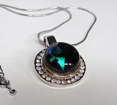 Green Flag é um colar delicado composto de um pingente de metal com cristais e uma gema de vidro artesanal ao centro. R$76