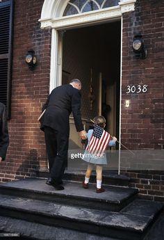 Jackie Kennedy Moves To Georgetown. En décembre 1963, à Georgetown, John John KENNEDY, âgé de trois ans, en manteau, un drapeau américain, à la main, de dos, entrant au N°3038 de N Street, accompagné d'un homme, le tenant par le bras.