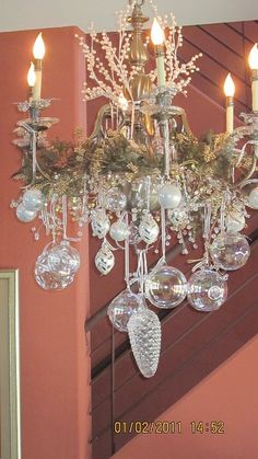 Sparkling crystal ornaments are hung from a light green wreath attached to the chandelier. I can only imagine that this is stunning in the evening with only the chandelier light bouncing off of the crystal ornaments.. . candles on the table - perhaps surrounded by more crystal ornaments and glassware - would only add to the magic. @KD Eustaquio Scarbrough