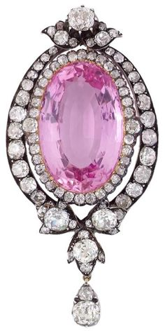 Important Victorian pink topaz and diamond pendant.  UK,  Mid 19th century.  Designed as a central oval-shaped topaz weighing 39.18 carats, within a surround of stylised foliate design in gold-backed silver set with circular-cut diamonds, mid 19th Century.    Listing via 1stdibs.