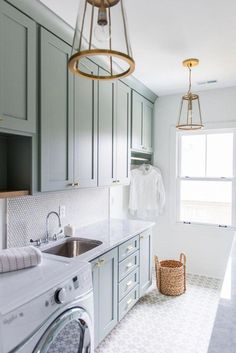 Gray green laundry room cabinets accented with brass knobs are fixed above a curved stainless steel sink paired with a p Laundry Room Lighting, Laundry Room Tile, Laundry Room Layouts, Laundry Room Remodel, Laundry Room Cabinets, Farmhouse Laundry Room, Room Tiles, Laundry Room Organization, Laundry Room Design