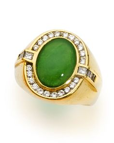 A jadeite jade and diamond ring  centering an oval cabochon jade within a surround of round brilliant-cut diamonds completed by modified square and baguette-cut diamond shoulders and a broad mount; mounted in eighteen karat gold