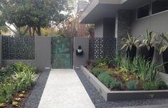 jardin avec des plantes succulentes, allée en béton et gravier et une porte en acier