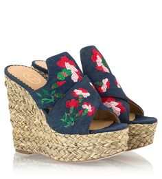 """Made from faded dark-blue denim Ash's """"Bahia"""" mule sandals are appliquéd with beautiful floral embroidery along the straps. They are set on a high espadrille wedge heel and platform and have a leather sole for extra grip. Wear yours on vacation with everything from floaty dresses to printed shorts."""